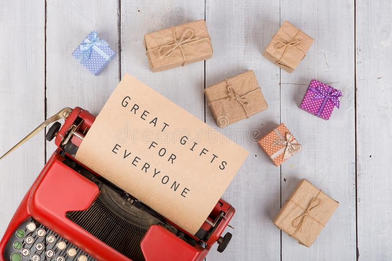 "Holidays concept - red typewriter with craft paper and text ""Great gifts for everyone"", gift boxes stock photo"
