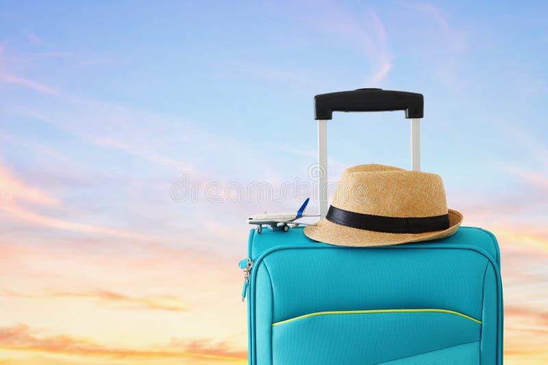 holidays concepto del recorrido juguete azul de la maleta y del aeroplano delante del fondo de la puesta del sol imagenes de archivo