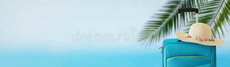 holidays concepto del recorrido maleta azul con el sombrero femenino delante del fondo tropical bandera imagen de archivo