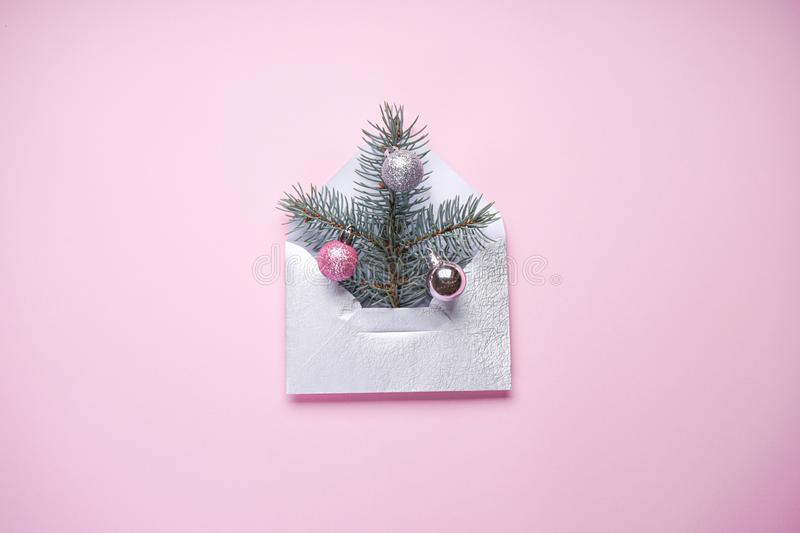 Christmas tree in the envelope, the minimum Christmas card, fir branch with colored Christmas balls on a pink background. royalty free stock photos