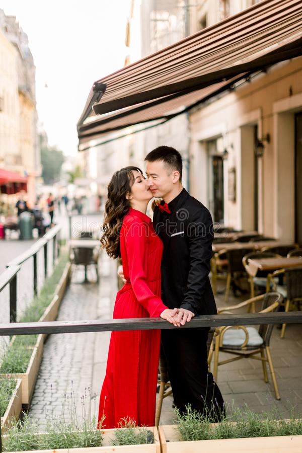 Holidays, dating and love story wedding concept - beautiful Asian couple holding hands and kissing in cafe in the old stock image