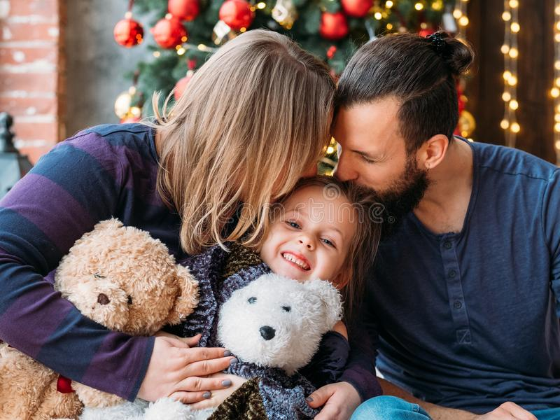 Holidays family leisure loving parents daughter. Holidays family leisure. Loving parents kissing their cute little daughter. Girl smiling, sitting happy with her royalty free stock photos