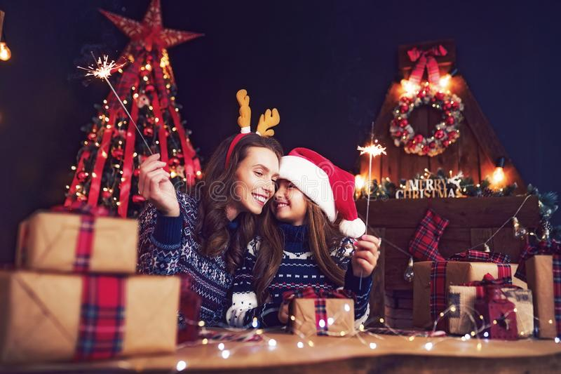 Holidays, family and people concept. Happy mother and little girl in santa helper hat with sparklers in hands, gift royalty free stock photography