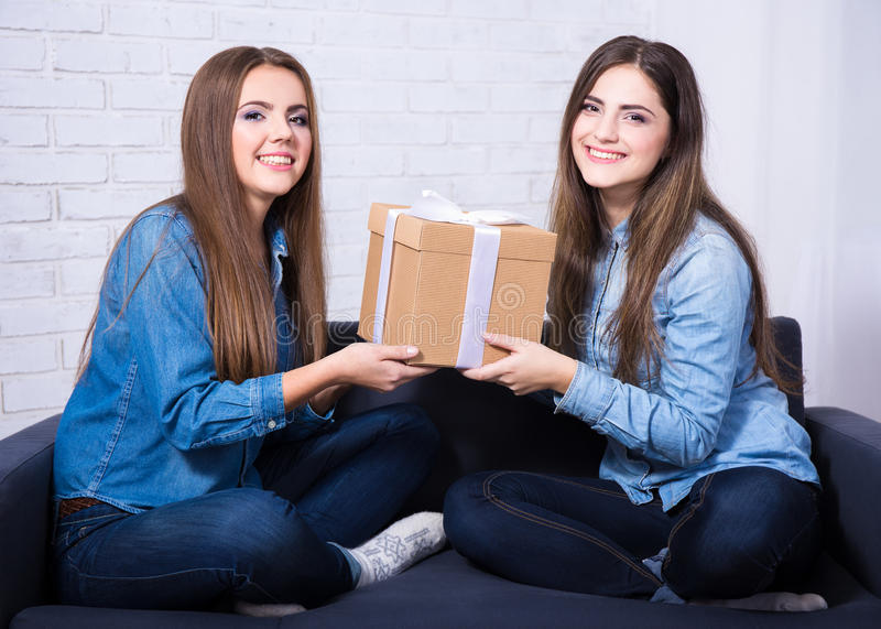 Holidays and friendship - happy girls with gift box sitting on s stock photos