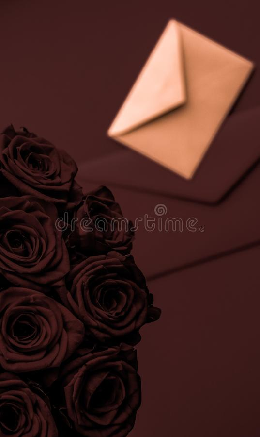 Love letter and flowers delivery on Valentines Day, luxury bouquet of roses and card on chocolate background for romantic holiday royalty free stock photography