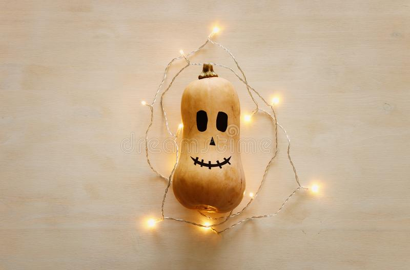 Holidays Halloween image. Cute and scary face of pumpkin and gold garlan lights over wooden white table. top view, flat lay royalty free stock images