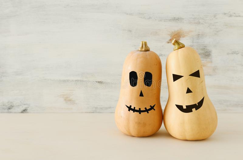 Holidays Halloween image. Cute and scary face of pumpkin over wooden white table royalty free stock photos