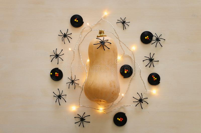 Holidays Halloween image. pumpkin and gold garlan lights over wooden white table. top view, flat lay royalty free stock images
