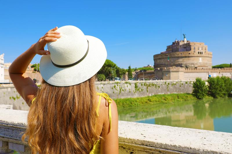 Holidays in Italy. Back view of beautiful tourist girl in Rome, Italy. Attractive fashion woman looks at Castel Sant Angelo castle. On the bridge stock photo