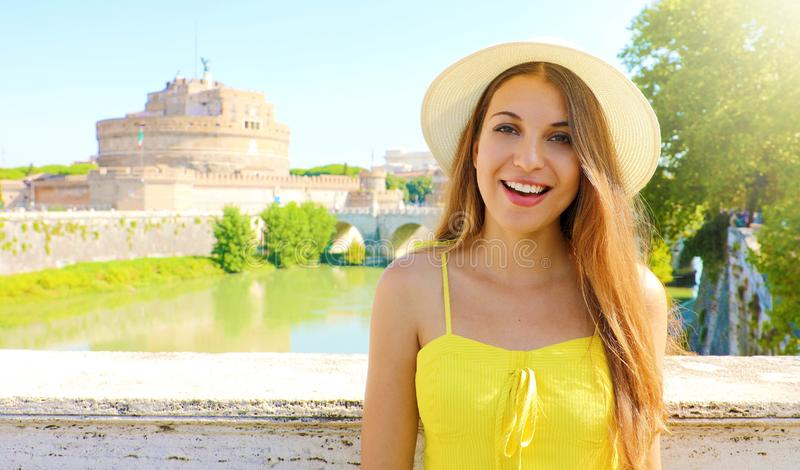 Holidays in Italy. Smiling beautiful tourist girl in Rome, Italy. Attractive fashion woman with Castel Sant Angelo castle on the. Background royalty free stock photo