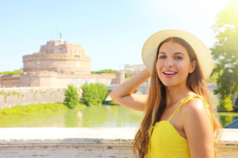Holidays in Italy. Smiling beautiful tourist girl in Rome, Italy. Attractive fashion woman with Castel Sant Angelo castle on the. Background stock photo