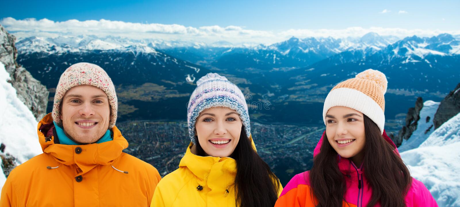 Happy friends in winter over alps mountains royalty free stock photography