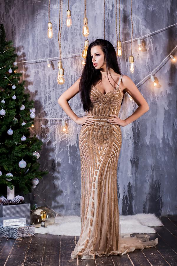 Holidays, celebration and people concept - young brunette woman in elegant dress over christmas interior background. Holidays, New Year, celebration and people stock image