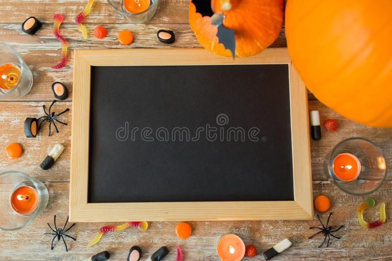 Blank chalkboard and halloween decorations. Holidays, school and party concept - halloween pumpkins, decorations with blank chalkboard on wooden boards royalty free stock photo
