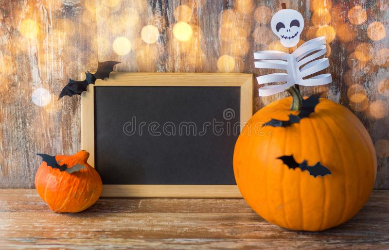 Blank chalkboard and halloween decorations. Holidays, school and party concept - halloween pumpkins, decorations with blank chalkboard on wooden boards royalty free stock photos