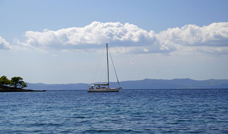 Holidays at sea. Pleasure yacht on the horizon. September in Greece. Sithonia. Blue sea and white clouds boat stock photos