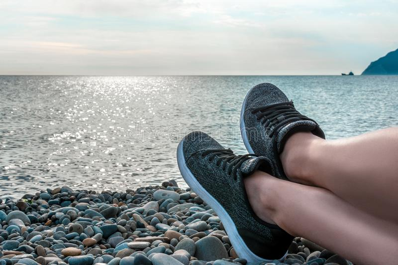Holidays at sea, vacation and travel concept-young girl resting lying on the sea, legs in sneakers close-up, summer adventures, stock images
