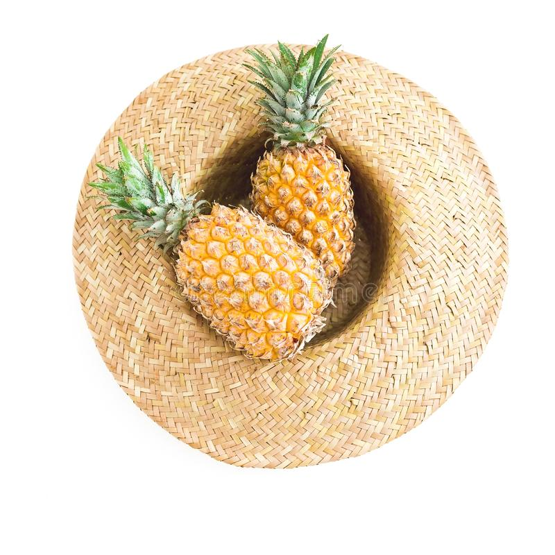 Holidays summer concept. Pineapple fruit and straw hat on white background stock image