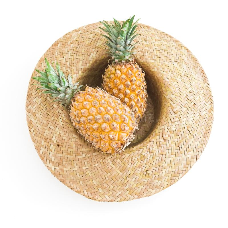 Holidays summer concept. Pineapple fruit and straw hat on white background. Flat lay, top view. royalty free stock photography