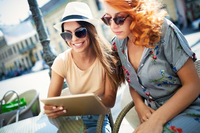 Holidays, tourism and internet - beautiful girls looking at tablet pc in cafe outside. Holidays, tourism and internet - beautiful young girls looking at tablet stock photography