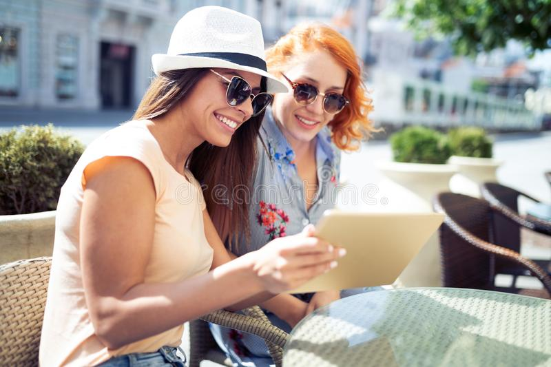 Holidays, tourism and internet - beautiful girls looking at tablet pc in cafe outside. Holidays, tourism and internet - beautiful young girls looking at tablet stock image