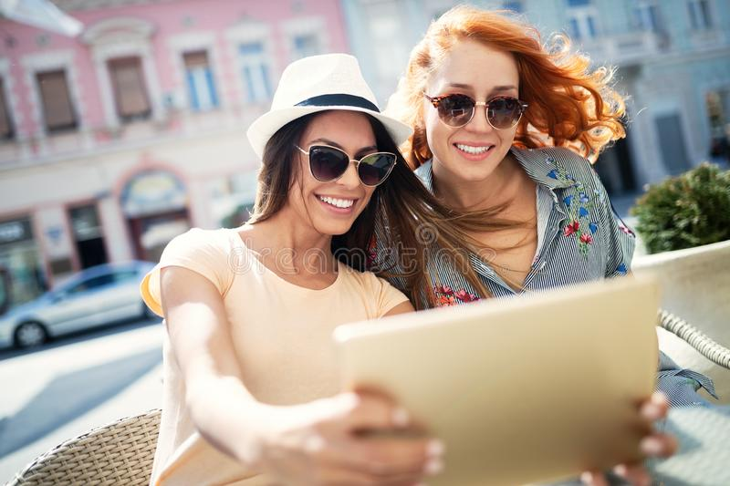 Holidays, tourism and internet - beautiful girls looking at tablet pc in cafe outside. Holidays, tourism and internet - beautiful young girls looking at tablet stock photo