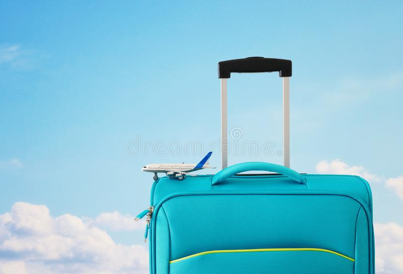 Holidays. travel concept. blue suitcase and airplane toy infront of sky background.  stock images