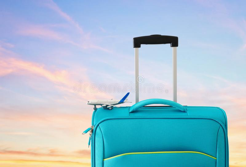Holidays. travel concept. blue suitcase and airplane toy infront of sunset sky background.  royalty free stock photos