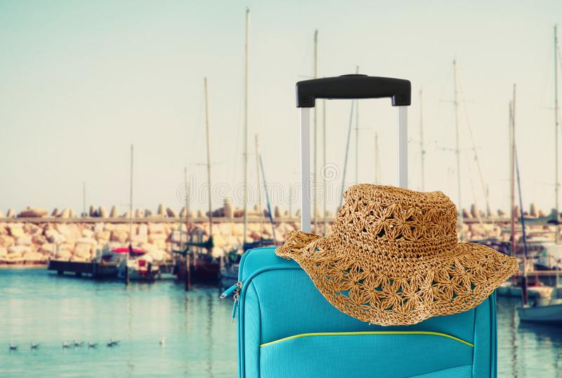 Holidays. travel concept. blue suitcase infront of marina background.  royalty free stock photos