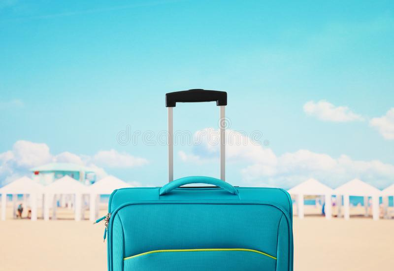 Holidays. travel concept. blue suitcase infront of tropical background.  stock images