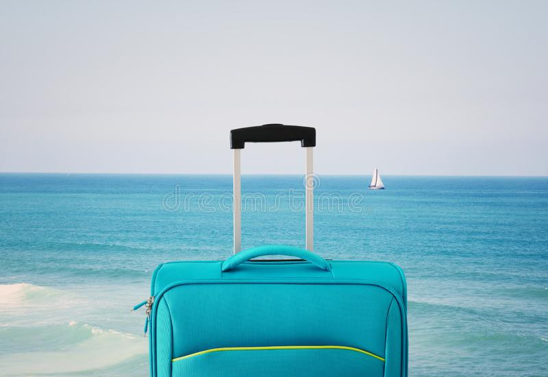 Holidays. travel concept. blue suitcase infront of tropical background.  stock photo