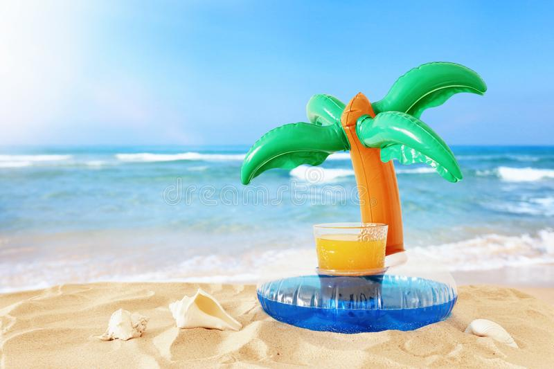 Holidays. vacation and summer concept with fresh fruit drink and palm shape pool float over sand at the beach stock photo