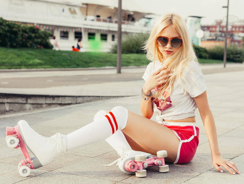 Holidays and vacations. A looker leggy long-haired young blonde woman in a vintage roller skates, sunglasses, T-shirt shorts sitti stock photos