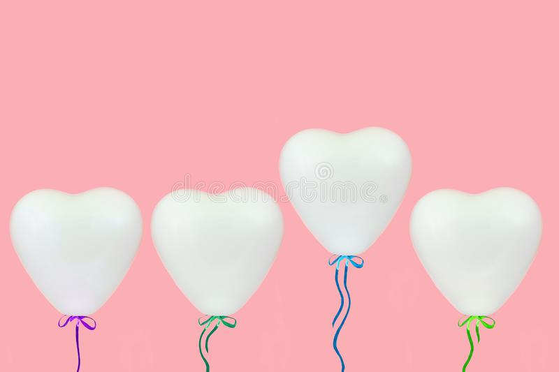 Holidays, valentines day and party decoration concept - white heart shaped balloons over pastel coral pink background stock image