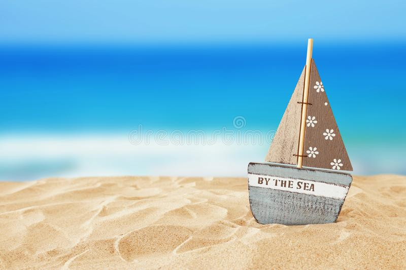 Holidays. vintage wooden boat over beach sand and sea landscape background stock photo