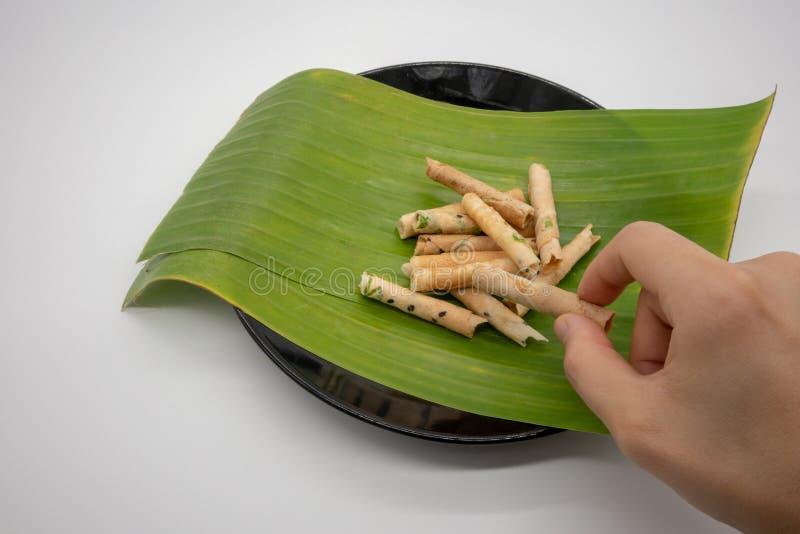 Holidng руки скручиваемость печенья кокоса, крены риса, на лист банана стоковое фото rf