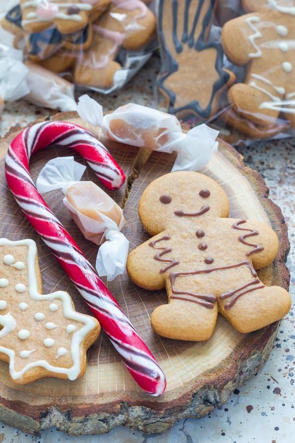holiydays的甜礼物 自创圣诞节姜饼曲奇饼和焦糖糖果在木板,垂直 免版税库存图片