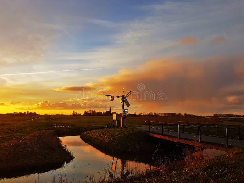 Holländische Windmühle am Sonnenaufgang stockfotos