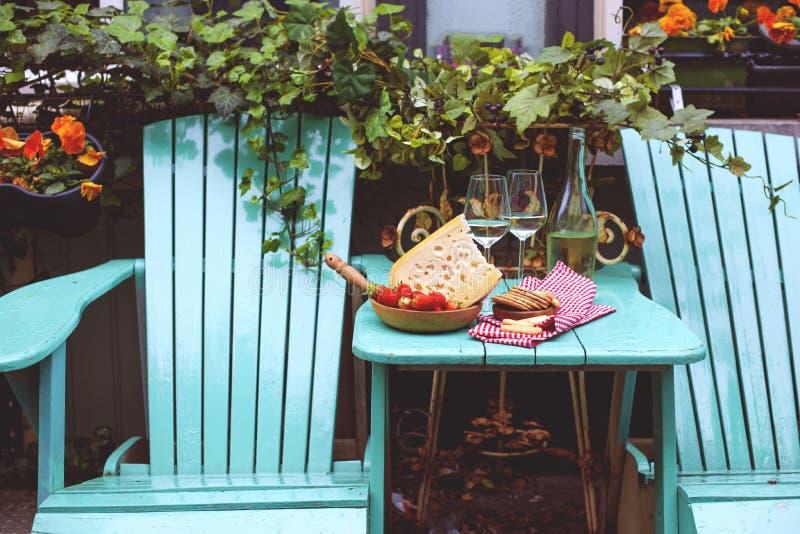 Holländischer Käse mit Löchern und Erdbeere Weißwein in einem Glas und in den Snäcken Lebensmittel auf dem Balkon, Kopienraum lizenzfreie stockfotos