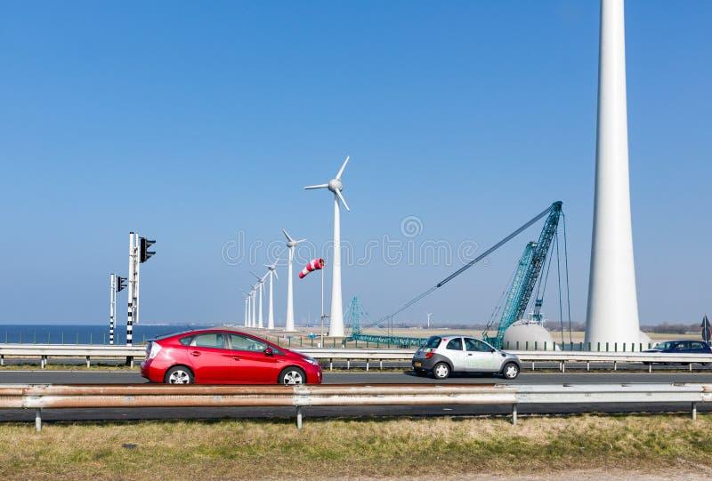 Holländsk huvudväg med bilar längs turbiner för vind för konstruktionsplats arkivfoto