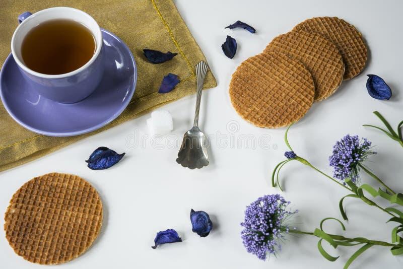 Holländsk karamellkaka Stroopwafel för kopp te i purpurfärgade blommor, på den vita tabellen royaltyfria foton