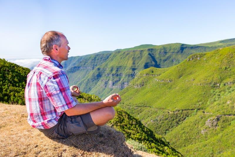 Holländsk man som mediterar på berget nära den gröna dalen arkivfoton
