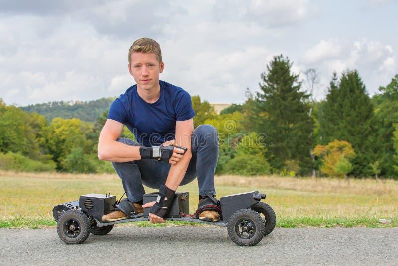 Holländsk pojke som kör elektrisk mountainboard i natur royaltyfri foto