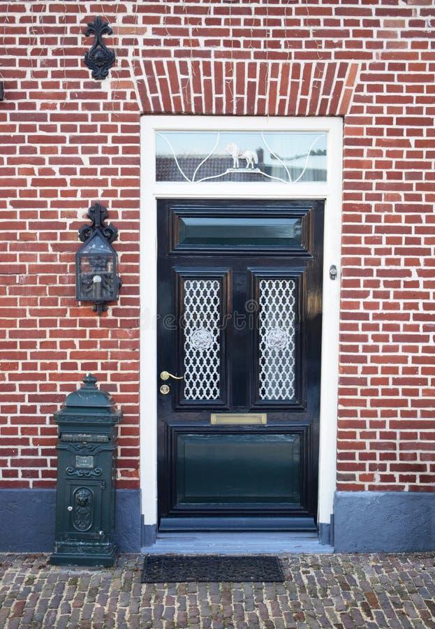 Holländsk ytterdörr med brevlådan och lyktan white för struktur för bakgrundstegelstenhus arkivbilder