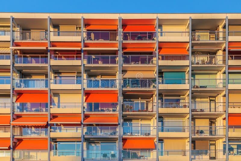 Holländskt flerbostadshus med orange parasoller royaltyfri bild