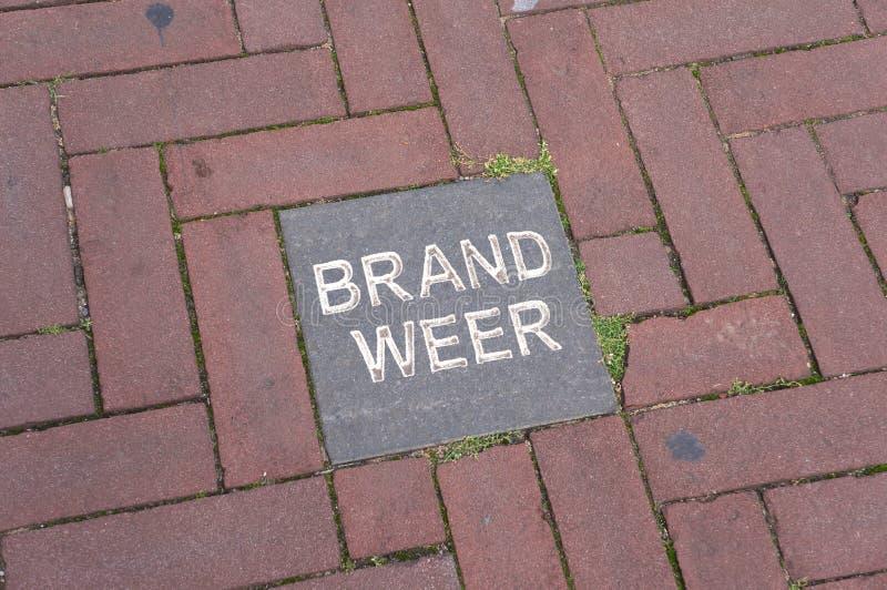 Holländskt ord Brandweer på en tegelplatta royaltyfri foto