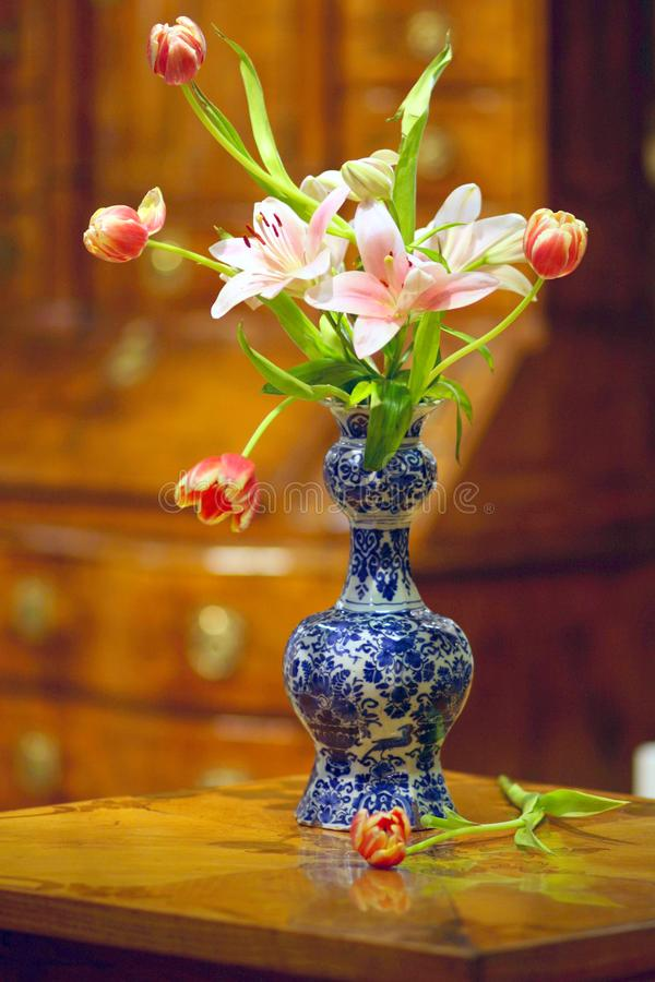 Holland antique delft vase with tulips and lilies stock images