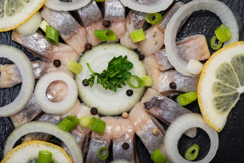 Hollandse Nieuwe- traditionell holländsk mat Öst rå sill som blöts i mild marinad Garnerat med citronen, löken och persilja arkivfoto