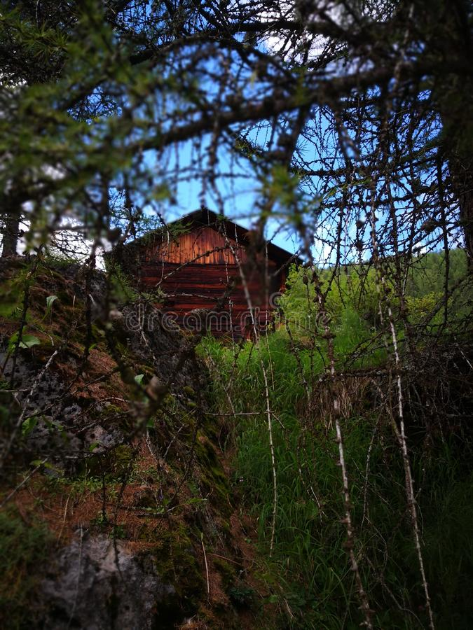 Hollibilly glimpse. Mountains Glimpse with a wooden cottage stock photo