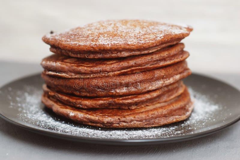 Holliday Breakfast Chocolate Pancakes dans le plat noir Poudre de sucre Fond clair Front View images stock